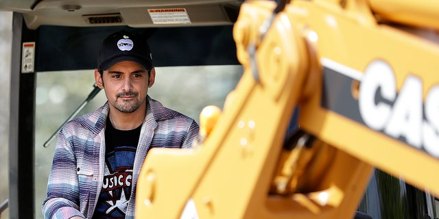 Country music star Brad Paisley operates a backhoe as he breaks ground for The Store, a free grocery store for people in need, on Wednesday, April 3, 2019, in Nashville, Tenn.