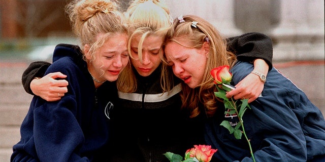 In this April 1999 file photo, Rachel Ruth, Rhianna Cheek and Mandi Annibel, all 16-year-old sophomores at Heritage High School in Littleton, Colo., console each other during a vigil service to honor the victims of the shooting spree in Columbine High School. (Associated Press)