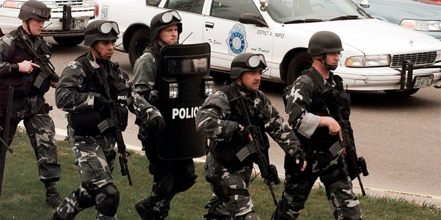 Members of a police SWAT team march to Columbine High School on April 20, 1999.