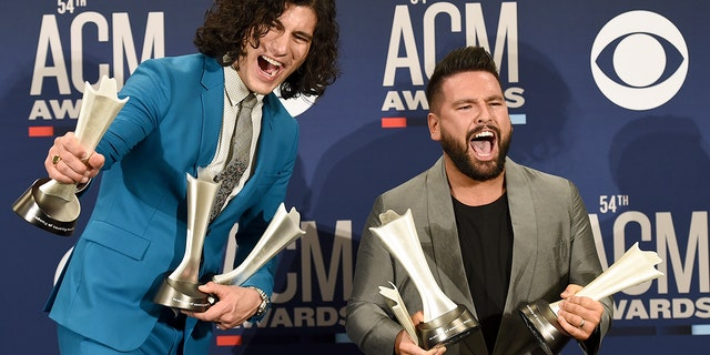 """Dan Smyers, left, and Shay Mooney, of Dan + Shay, pose in the press room with the awards for song of the year and single of the year for """"Tequila,"""" and duo of the year at the 54th annual Academy of Country Music Awards at the MGM Grand Garden Arena on Sunday, April 7, 2019, in Las Vegas. (Photo by Jordan Strauss/Invision/AP)"""