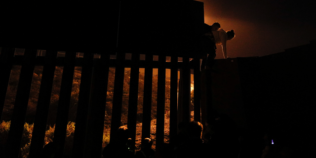 FILE - In this Dec. 2, 2018, file photo, Honduran migrants climb over a section of the U.S. border fence from Playas of Tijuana, Mexico, before handing themselves in to border control agents. A surge in family arrivals, largely from Guatemala and Honduras, has led Border Patrol agents to shift attention from preparing criminal cases to caring for children. (AP Photo/Rebecca Blackwell, File)