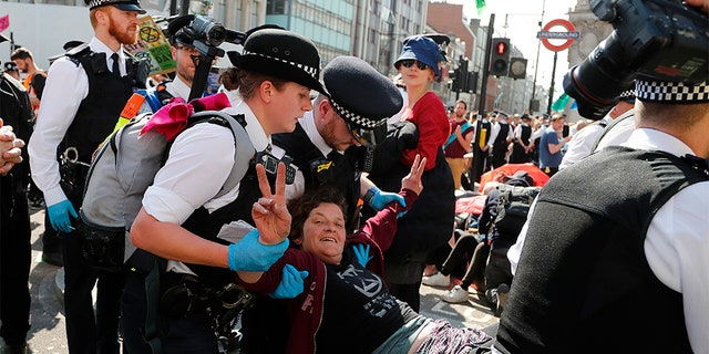 Police arrest protesters at Oxford Circus in London on Friday.