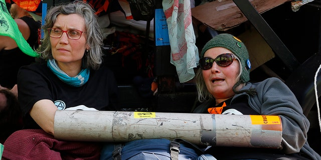 Protesters chained themselves onto a boat in Oxford Circus in London on Friday as part of the ongoing climate action-related demonstrations. (AP)