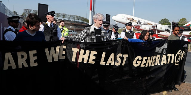 Police surround environmental protestors near Heathrow Airport in London on Friday.