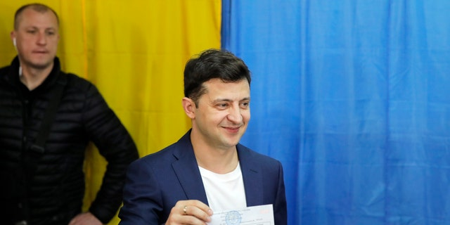Ukrainian comedian and presidential candidate Volodymyr Zelenskiy shows his ballot before casting his ballot at a polling station, during the second round of presidential elections in Kiev, Ukraine, Sunday, April 21, 2019. Top issues in the election have been corruption, the economy and how to end the conflict with Russia-backed rebels in eastern Ukraine. (AP Photo/Vadim Ghirda)