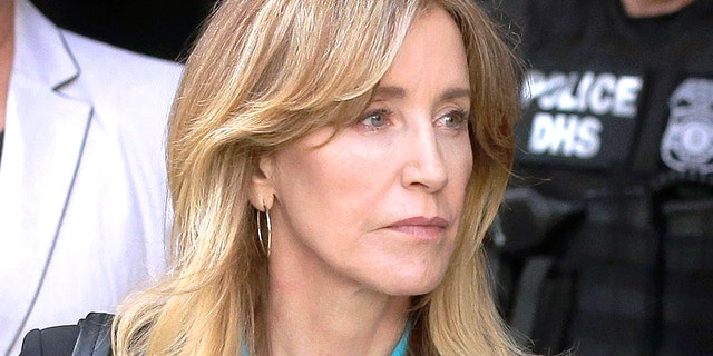 FILE - In this April 3, 2019 file photo, actress Felicity Huffman arrives at federal court in Boston to face charges in a nationwide college admissions bribery scandal. In a court filing on Monday, April 8, 2019, Huffman agreed to plead guilty in the cheating scam.