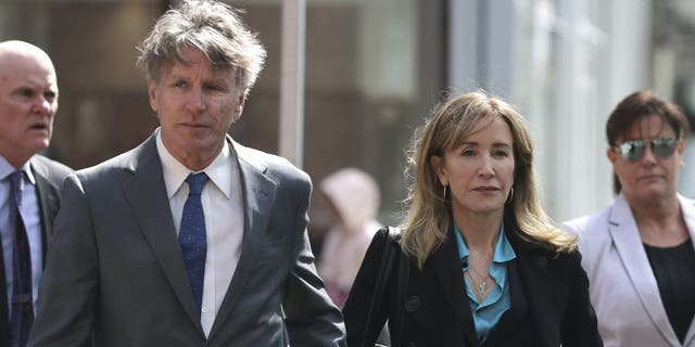 Actress Felicity Huffman arrives holding hands with her brother Moore Huffman Jr., left, at federal court in Boston on Wednesday, April 3, 2019, to face charges in a nationwide college admissions bribery scandal.