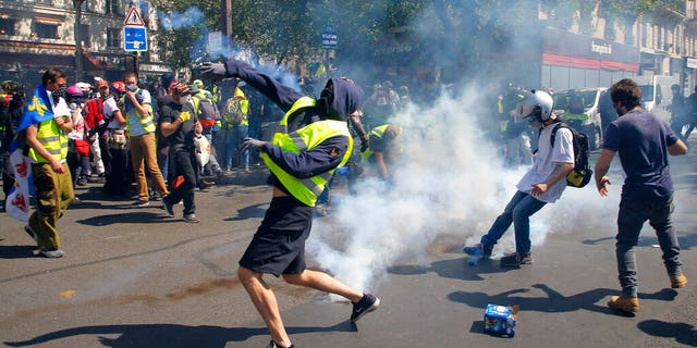 A demonstrator throws back a tear gas canister during a Yellow Vest demonstration in Paris, Saturday, April 20, 2019.