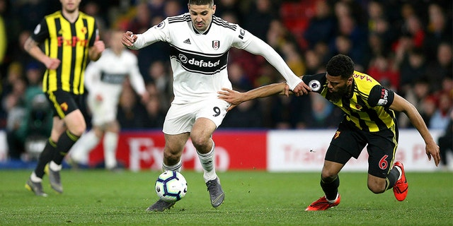 Fulham's Aleksandar Mitrovic, center, and Watford's Adrian Mariappa battle for the ball during their English Premier League soccer match at Vicarage Road, Watford, England, Tuesday, April 2, 2019. (Nigel French/PA via AP)