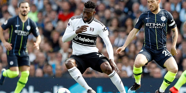 Manchester City's David Silva, right, vies for the ball with Fulham's Andre-Frank Zambo Anguissa during the English Premier League soccer match between Fulham and Manchester City at Craven Cottage stadium in London, Saturday, March 30, 2019. (AP Photo/Alastair Grant)