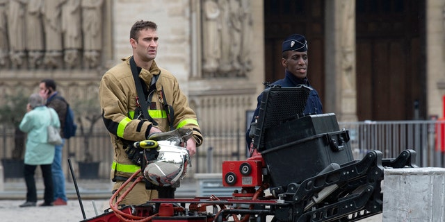 Firefighters are seen with a robot firefighter called Colossus, made by French robotics company Shark Robotics, outside Notre-Dame Cathedral after a major fire yesterday on April 16, 2019, in Paris, France.