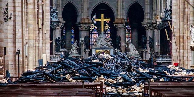 دیدگاهی از آوار درون نتردام د پاریس در اثر آتش سوزی که کلیسای جامع را ویران کرد، در طی دیدار وزیر کشور فرانسه، کریستوف کاستنر (در تصویر نیست) در پاریس، فرانسه، 16 آوریل 2019. کریستف پتی تسون / استخر از طریق REUTERS - RC12F77ABC70