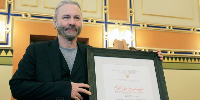 Bruce Dickinson poses for cameras with his honorary citizen certificate at the city hall in Sarajevo, Bosnia-Herzegovina, Saturday, April 6, 2019. Bosnia's capital Sarajevo has declared Iron Maiden lead singer Bruce Dickinson an honorary citizen in gratitude for the concert the heavy metal band held while the city was under siege during 1992-95 war.