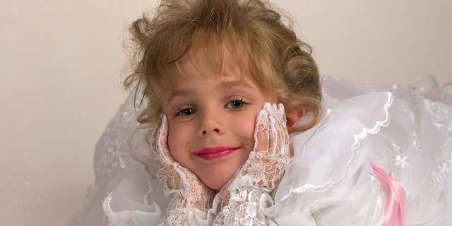 May 1, 1994 - JonBenet Ramsey, very happy, all in white, wearing white lace gloves laying down on a white seamless at a studio session for a commercial ad and actress portfolio.