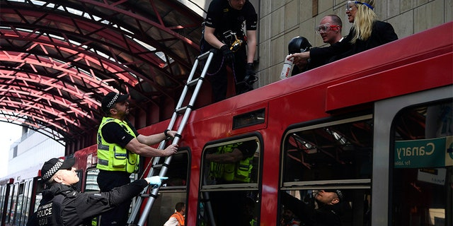 The police are removing environmental activists who have stuck to a Dockland Light Railway train at Canary Wharf station in eastern London in the wake of ongoing protests against climate change.