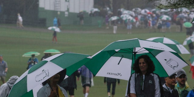 Fans use umbrellas near the ninth hole during the second round for the Masters golf tournament Friday, April 12, 2019, in Augusta, Ga. (AP Photo/Charlie Riedel)