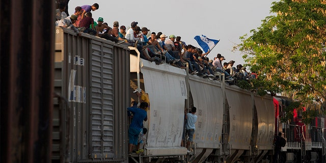 Central American migrants ride atop a freight train during their journey toward the U.S.-Mexico border, in Ixtepec, Oaxaca State, Mexico, on Tuesday.