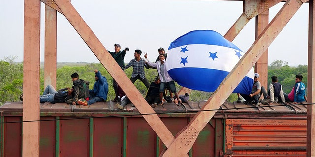 "Central American migrants hold Honduras' national flag, while moving in a caravan through Juchitan, Oaxaca atop a train known as ""The Beast"" towards the United States, in Mexico April 26, 2019."