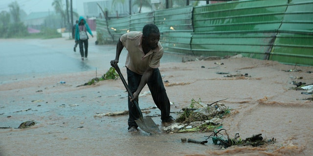 A man clears rubble on a street, in Pemba, on the northeastern coast of Mozambique, Sunday, April, 28, 2019. Serious flooding began on Sunday in parts of northern Mozambique that were hit by Cyclone Kenneth three days ago, with waters waist-high in areas, after the government urged many people to immediately seek higher ground. (AP)