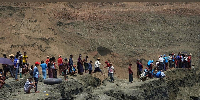 Local people look on in a jade mine where the mud dam collapsed in Hpakant, Kachin state, Myanmar April 23, 2019.