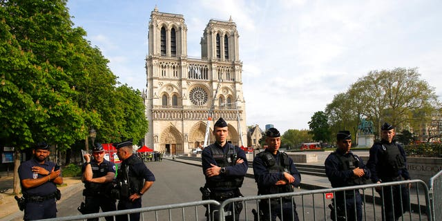 Police officers stand behind the security barriers in front of Notre Dame cathedral Thursday, April 18, 2019 in Paris.