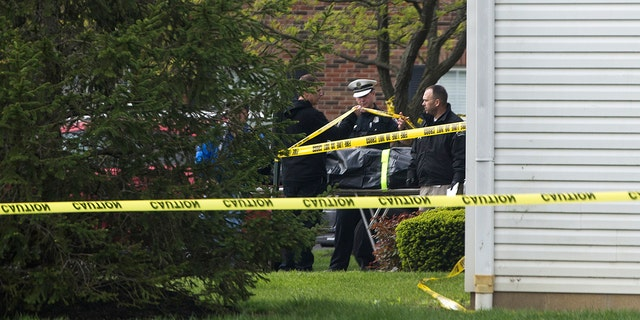 A body is loaded into a Butler County coroner's van Monday, April 29, 2019 after multiple people were found dead at the Lakefront at West Chester apartment complex in West Chester Township, Ohio on Sunday night, according to police.