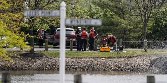 Police authorities search a nearby pond at a scene at an apartment complex Monday, April 29, 2019, in West Chester, Ohio.