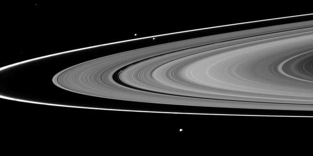 Saturn's moons Prometheus, Pandora and Epimetheus can be seen among the planet's rings in this image from the Cassini spacecraft. New views of Pan, Dasphnis, Atlas, Pandora and Epimetheus have suggested possible reasons for the strange shapes and colors of those moons.