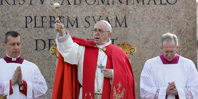 Pope Francis asperses holy water as he celebrates Palm Sunday Mass in St. Peter's Square at the Vatican, Sunday, April 14, 2019.