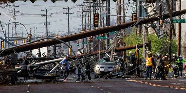 Two people were trapped in the SUV for about an hour after several power poles came crashing down on East Marginal Way on Friday, according to Tukwila police. (Ellen M. Banner/The Seattle Times via AP)