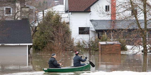People paddle a canoe on the flooded streets in Sainte-Marie, Quebec, Saturday, April 20, 2019. The Chaudiere River burst its banks after heavy rain.