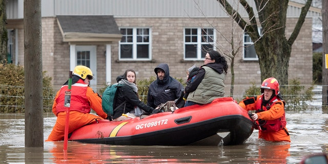 People are evacuated by firefighters in a boat in Sainte-Marie, Quebec, Saturday, April 20, 2019. The Chaudiere River burst its banks after heavy rain.