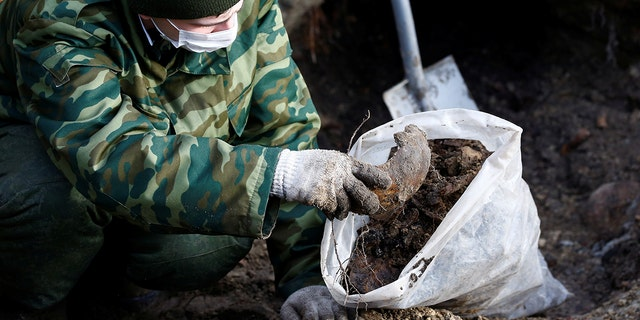 """A soldier from a special """"search battalion"""" of Belarus Defence Ministry takes part in the exhumation of a mass grave containing the remains of about 730 prisoners of a former Jewish ghetto, discovered at a construction site in the center of Brest, Belarus February 26, 2019. REUTERS/Vasily Fedosenko - RC1569C86700"""
