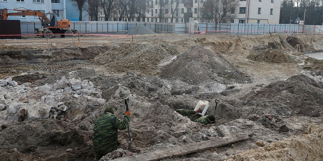 """Soldiers from a special """"search battalion"""" of Belarus Defence Ministry take part in the exhumation of a mass grave containing the remains of about 730 prisoners of a former Jewish ghetto, discovered at a construction site in the center of Brest, Belarus February 26, 2019."""