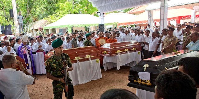 A soldier stands guard during a funeral service attended by Cardinal Malcolm Ranjith for Easter Sunday bomb blast victims at St. Sebastian Church in Negombo, Sri Lanka, on Tuesday. (AP)