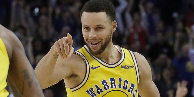 Golden State Warriors guard Stephen Curry (30) points toward teammate Alfonzo McKinnie after Curry scored against the Denver Nuggets during the second half of an NBA basketball game in Oakland, Calif., Tuesday, April 2, 2019. (Associated Press)