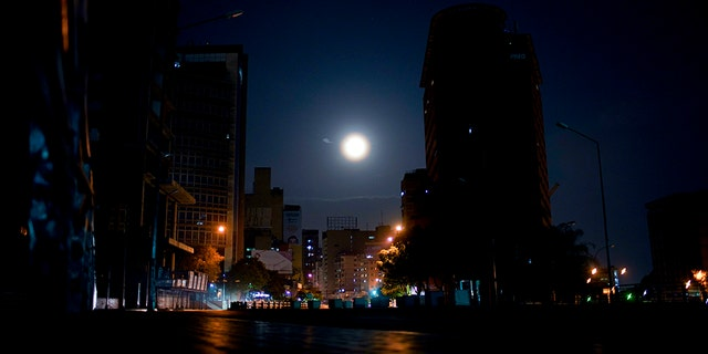 The moon rises above an empty avenue in Caracas, Venezuela, late Thursday, March 21, 2019. Residents avoid stepping outside their homes due to crime, or for lack of anything to spend. (AP Photo/Natacha Pisarenko)