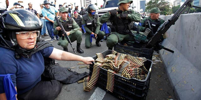 An anti-government protester sits by ammunition being used by rebel troops rising up against the government of Venezuela's President Nicolas Maduro as they all take cover on an overpass outside La Carlota military airbase where the rebel soldiers confront loyal troops inside the base in Caracas, Venezuela.