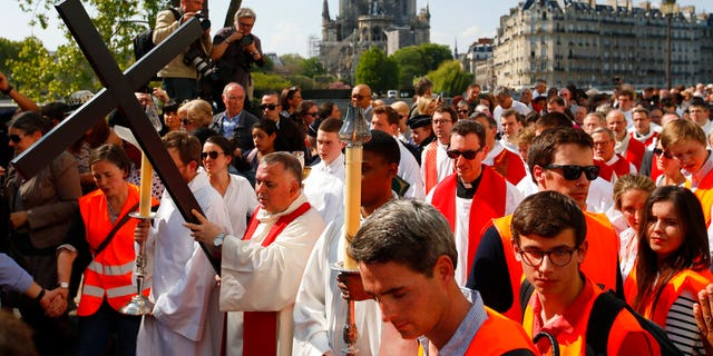 With Notre Dame cathedral in background, religious officials carry the cross during the Good Friday procession, Friday, April 19, 2019 in Paris.