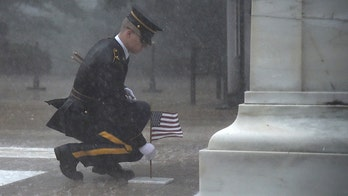 Soldier seen placing flag at Tomb of Unknown Soldier during torrential rain