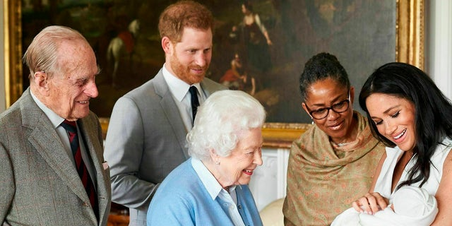 In this image made available by SussexRoyal on Wednesday May 8, 2019, Britain's Prince Harry and Meghan, Duchess of Sussex, joined by her mother Doria Ragland, show their new son to Queen Elizabeth II and Prince Philip at Windsor Castle, Windsor, England. Prince Harry and Meghan have named their son Archie Harrison Mountbatten-Windsor.