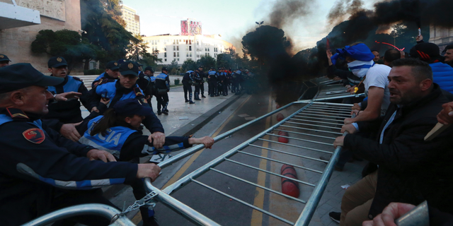 Protesters try to remove a metal fence during clashes with police outside the Government building in Tirana, Saturday, May 11, 2019. Thousands of supporters of the Albania's center-right opposition protested in Tirana Saturday, calling for the left-wing government to resign and for an early parliamentary election. (AP Photo/Hektor Pustina)