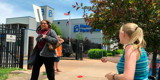 Anti-abortion activist Teresa Pettis, right, greets a passerby outside the Planned Parenthood clinic in St. Louis. last month. (AP Photo/Jim Salter, File)