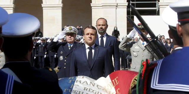 French President Emmanuel Macron honors the late special forces soldiers Cedric de Pierrepont and Alain Bertoncello, who were killed in a night-time rescue of four foreign hostages including two French citizens in Burkina Faso last week, during a national tribute at the Invalides, in Paris, Tuesday, May 14, 2019. France is honoring two special forces officers killed in an operation that freed four hostages held in Burkina Faso.