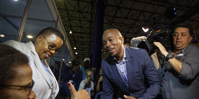 Mmusi Maimane, leader of the largest opposition party, the Democratic Alliance, is greeted by a supporter as he visits the Independent Electoral Commission Results Center in Pretoria, South Africa Thursday, May 9, 2019. South Africans voted Wednesday in a national election and preliminary results show that the ruling African National Congress party (ANC) has an early lead in the national elections but has seen its share of the vote drop significantly.