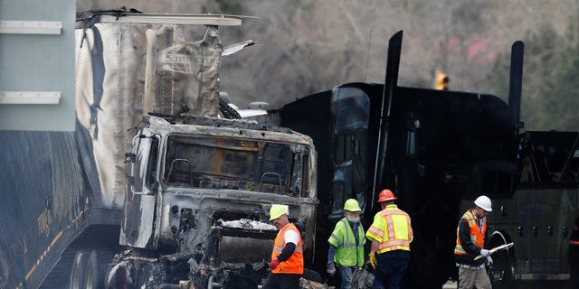 FILE - In this April 26, 2019, file photo, workers clear debris on Interstate 70 in Lakewood, Colo., from a pileup involving a semitrailer hauling lumber that killed four people. The driver of the truck told investigators that his brakes were not working. The Texas company that owns the semitrailer had two different trucks temporarily taken out of service for brake-related problems in the last year, according to federal safety records. (AP Photo/David Zalubowski, File)