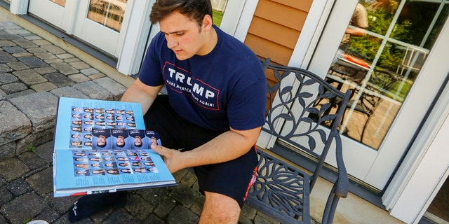 """In this June 2017 photo, Wall High School student Grant Berardo is seen flipping through his 2017 school yearbook. The yearbook included a photo of him wearing a digitally altered T-shirt that originally included the words """"Trump Make America Great Again."""""""