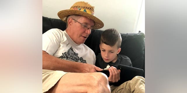 """This summer 2018 photo provided by Al Mattin on Friday, May 10, 2019 shows his father, Stephen, and son, Ronan, at Stephen's home in Kensington, N.H. The Handel & Haydn Society had just finished a rendition of Mozart's """"Masonic Funeral"""" at Boston's Symphony Hall on Sunday, May 5, 2019 when a youngster blurted out: """"WOW!"""""""