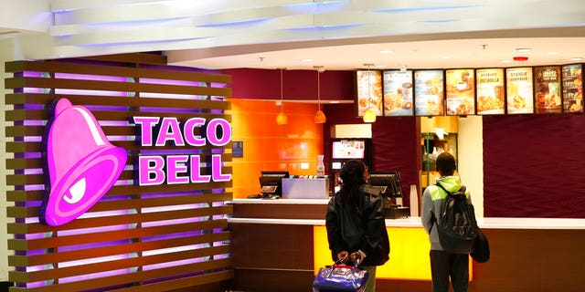 FILE: Travelers look at a menu at a Taco Bell restaurant inside Miami International Airport in Miami. (Associated Press)
