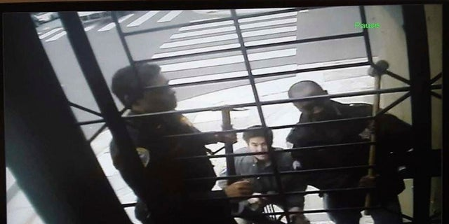 In this May 10 image from video provided by Bryan Carmody, San Francisco police armed with sledgehammers execute a search warrant at his home. (Bryan Carmody/@bryanccarmody via AP)